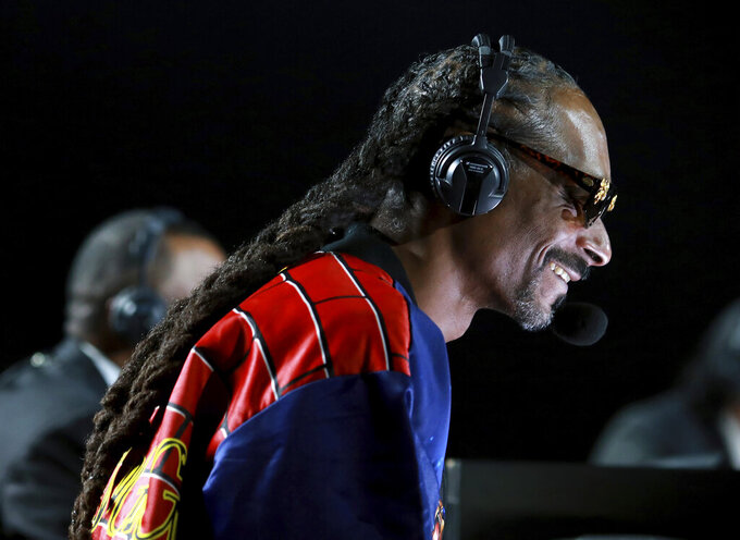 In a photo provided by Triller, Snoop Dogg performs onstage at an exhibition boxing bout between Mike Tyson and Roy Jones Jr. on Saturday, Nov. 28, 2020, in Los Angeles. The bout was unofficially ruled a draw by the WBC judges at ringside. Tyson and Jones fought eight two-minute rounds, and both emerged smiling and apparently healthy from a highly unusual event. (Joe Scarnici/Triller via AP)