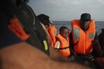 Six-year-old Quadri from Nigeria sits on a rescue boat next to his mother, left, in the Mediterranean Sea, Wednesday, Sept. 18, 2019. The Ocean Viking humanitarian ship operated by SOS Mediterranee and Doctors Without Borders pulled over 70 migrants from a rubber boat north of Libya. (AP Photo/Renata Brito)