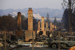 FILE - This Oct. 13, 2017 file photo shows a row of chimneys standing in a neighborhood devastated by the Tubbs fire near Santa Rosa, Calif. New California data shows insurance companies declined to renew nearly 350,000 home insurance policies in areas at high risk for wildfire since the state began collecting data in 2015. The data released this week did not say how many people who lost their insurance were able to purchase it elsewhere or how much more it cost. (AP Photo/Jae C. Hong, File)