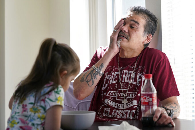 Leroy Pascubillo wipes away tears as he looks at his daughter, who was born addicted to heroin and placed with a foster family at birth, and talks about his journey regaining custody, May 10, 2021, in Seattle. Pascubillo, who had used drugs for the better part of four decades, was in a court-ordered in-patient drug rehab program when the pandemic first hit. (AP Photo/Elaine Thompson)
