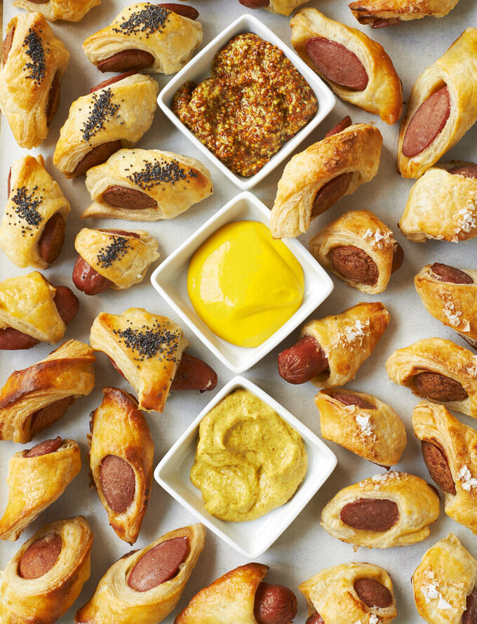 """This image provided by Martha Stewart Living shows pigs in blankets with mustard sauces. Greg Lofts, deputy food editor for Martha Stewart Living, says his years of catering experience for kids and adults alike """"taught me that the most precious, fancy and labor-intensive hors d'oeuvres will never be as popular as pigs in a blanket with ketchup and mustard for dunking. (David Malosh/Martha Stewart Living via AP)"""