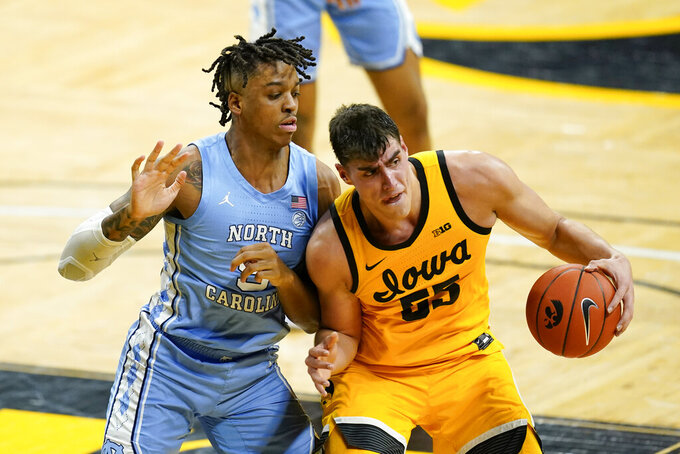 Iowa center Luka Garza, right, drives around North Carolina forward Armando Bacot during the second half of an NCAA college basketball game, Tuesday, Dec. 8, 2020, in Iowa City, Iowa. Iowa won 93-80. (AP Photo/Charlie Neibergall)