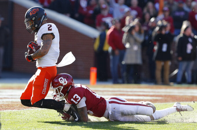 Oklahoma State wide receiver Tylan Wallace (2) is tackled by Oklahoma cornerback Tre Norwood (13) just before the end zone in the first quarter of an NCAA college football game in Norman, Okla., Saturday, Nov. 10, 2018. (AP Photo/Alonzo Adams)