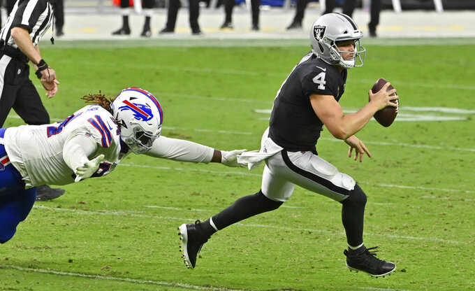 Las Vegas Raiders quarterback Derek Carr (4) avoids a tackle by the Buffalo Bills during the second half of an NFL football game, Sunday, Oct. 4, 2020, in Las Vegas. (AP Photo/David Becker)