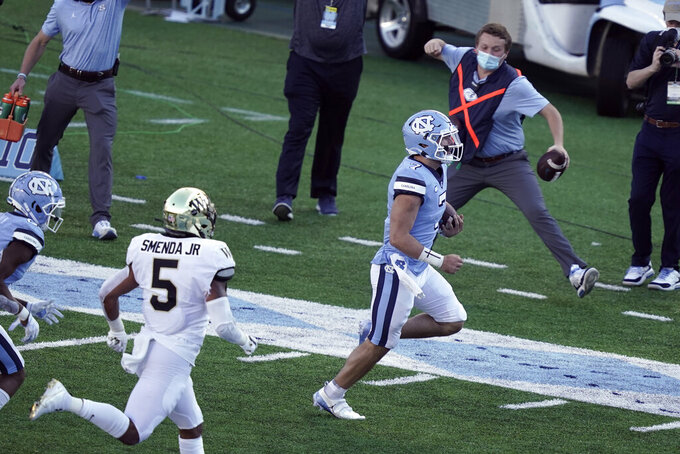 North Carolina quarterback Sam Howell (7) runs a touchdown as Wake Forest linebacker Ryan Smenda Jr. (5) chases during the second half of an NCAA college football game in Chapel Hill, N.C., Saturday, Nov. 14, 2020. (AP Photo/Gerry Broome)