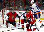 New York Islanders center Brock Nelson (29) attempts to deflect the puck past Ottawa Senators goaltender Craig Anderson (41) as Senators defenseman Nikita Zaitsev (22) defends during second-period NHL hockey game action in Ottawa, Ontario, Friday, Oct. 25, 2019. (Fred Chartrand/The Canadian Press via AP)