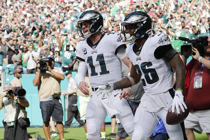 Philadelphia Eagles quarterback Carson Wentz (11) celebrates with running back Miles Sanders (26) after Sanders scored a touchdown during he first half of an NFL football game against the Miami Dolphins, Sunday, Dec. 1, 2019, in Miami Gardens, Fla. (AP Photo/Lynne Sladky)