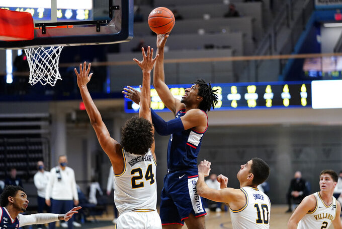 Connecticut's Isaiah Whaley, center, goes up for a shot between Villanova's Jeremiah Robinson-Earl, left, and Cole Swider during the second half of an NCAA college basketball game, Saturday, Feb. 20, 2021, in Villanova, Pa. (AP Photo/Matt Slocum)