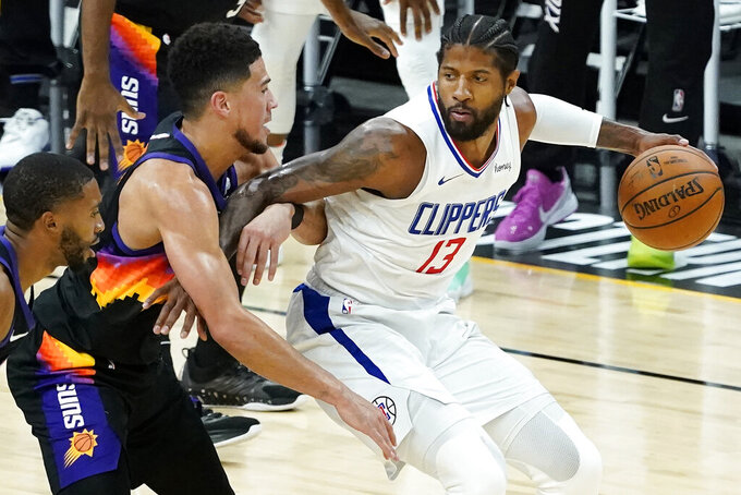 Los Angeles Clippers guard Paul George, right, is defended by Phoenix Suns guard Devin Booker during the first half of Game 2 of the NBA basketball Western Conference Finals, Tuesday, June 22, 2021, in Phoenix. (AP Photo/Matt York)