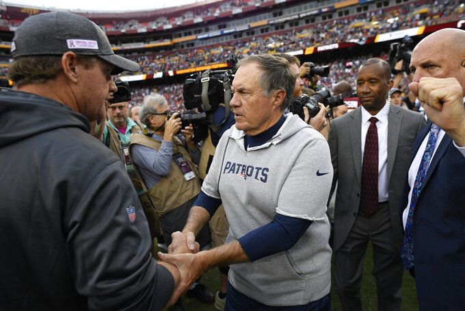 New England Patriots head coach Bill Belichick speaks with Washington Redskins head coach Jay Gruden after an NFL football game, Sunday, Oct. 6, 2019, in Landover, Md. The New England Patriots won 33-7. (AP Photo/Nick Wass)