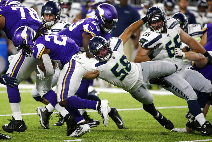Minnesota Vikings running back Mike Boone runs from Seattle Seahawks outside linebacker Austin Calitro (58) during the second half of an NFL preseason football game, Sunday, Aug. 18, 2019, in Minneapolis. (AP Photo/Bruce Kluckhohn)