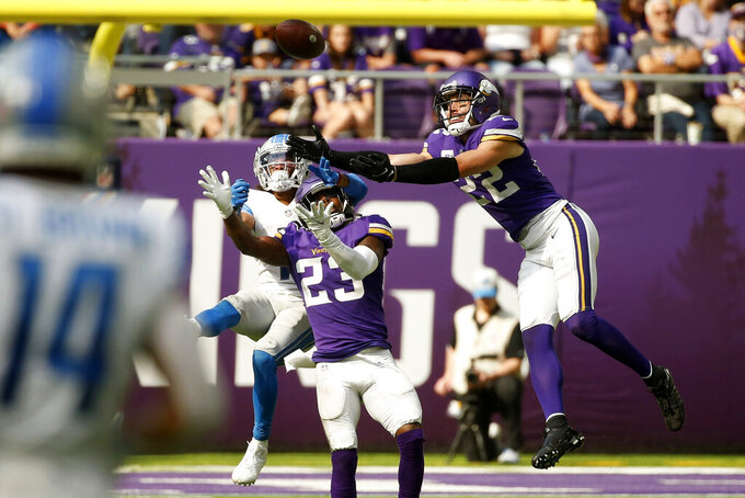 Minnesota Vikings free safety Xavier Woods (23) and safety Harrison Smith (22) break up a pass intended for Detroit Lions wide receiver Kalif Raymond, left, during the second half of an NFL football game, Sunday, Oct. 10, 2021, in Minneapolis. (AP Photo/Bruce Kluckhohn)