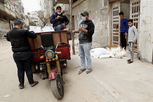 Palestinian workers distribute food supplies from the United Nations Relief and Works Agency (UNRWA) to a house, in the Sheikh Redwan neighborhood of Gaza City, Tuesday, March 31, 2020. The UN has resumed food deliveries to thousands of impoverished families in the Gaza Strip after a three-week delay caused by fears of the coronavirus (AP Photo/Adel Hana)