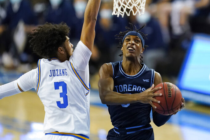 San Diego guard Marion Humphrey, right, goes up for a shot against UCLA guard Johnny Juzang during the first half of an NCAA college basketball game Wednesday, Dec. 9, 2020, in Los Angeles. (AP Photo/Ashley Landis)