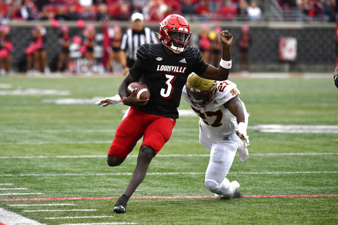 Louisville quarterback Malik Cunningham (3) runs from the grasp of Boston College linebacker Kam Arnold (27) during the first half of an NCAA college football game in Louisville, Ky., Saturday, Oct. 23, 2021. (AP Photo/Timothy D. Easley)