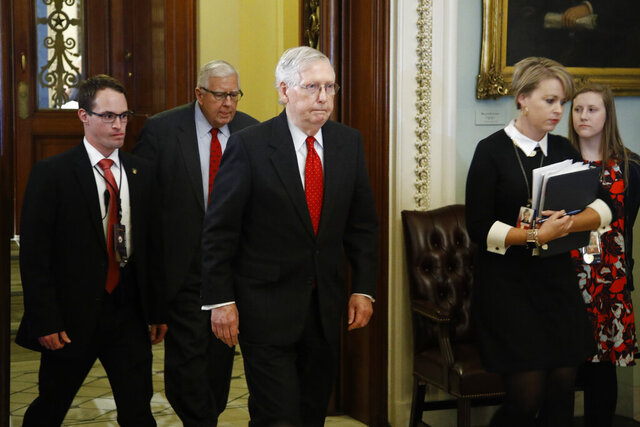 Senate Majority Leader Mitch McConnell, R-Ky., center, walks out of the Senate chamber at the Capitol Tuesday, Jan. 21, 2020, in Washington. President Donald Trump's impeachment trial quickly burst into a partisan fight Tuesday as proceedings began unfolding at the Capitol.  (AP Photo/Steve Helber)