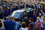"""Men in traditional dress of the island of Crete and people escort a hearse, ahead of the burial of the late Greek composer, Mikis Theodorakis, in Chania Crete island, Greece, Thursday, Sept. 9 2021. Theodorakis died Thursday, Sept. 2, 2021 at 96. He penned a wide range of work, from somber symphonies to popular TV and film scores, including for """"Serpico"""" and """"Zorba the Greek."""" He is also remembered for his opposition to the military junta that ruled Greece from 1967-1974, when he was persecuted and jailed and his music outlawed. (AP Photo/Michael Varaklas)"""