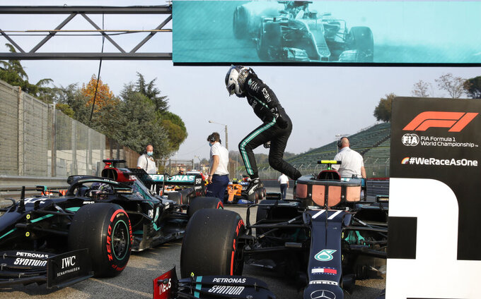 Mercedes driver Valtteri Bottas of Finland jumps out of his car after clocking the fastes time during qualification ahead of Sunday's Emilia Romagna Formula One Grand Prix, at the Enzo and Dino Ferrari racetrack, in Imola, Italy, Saturday, Oct. 31, 2020. (AP Photo/Luca Bruno, Pool)