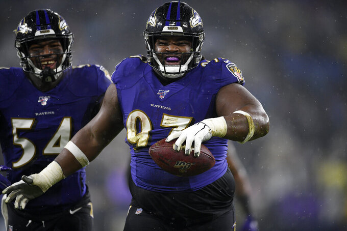 FILE - In this Sunday, Dec. 29, 2019, file photo, Baltimore Ravens defensive tackle Michael Pierce (97) celebrates his fumble recovery with linebacker Tyus Bowser (54) during the first half of an NFL football game against the Pittsburgh Steelers in Baltimore. After opting out of the 2020 season due to health concerns around COVID-19, Michael Pierce has returned to the Minnesota Vikings, eager to establish himself at a nose tackle position in need of help. (AP Photo/Nick Wass, File)