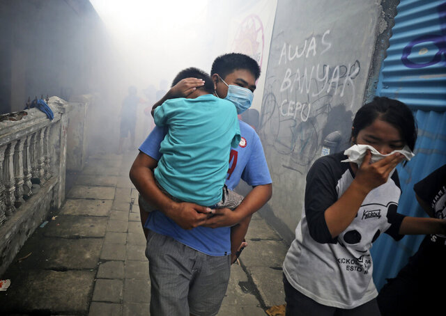 People move away as health workers fumigate a slum to prevent an outbreak of dengue fever in Jakarta, Indonesia, on Monday, March 23, 2020. While 2019 was the worst year on record for global dengue cases, experts fear an even bigger surge is possible because their efforts to combat it were hampered by restrictions imposed in the coronavirus pandemic. (AP Photo/Dita Alangkara)