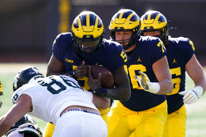 Michigan quarterback Joe Milton (5) is sacked by Michigan State defensive end Drew Beesley (86) during the first half of an NCAA college football game, Saturday, Oct. 31, 2020, in Ann Arbor, Mich. (AP Photo/Carlos Osorio)