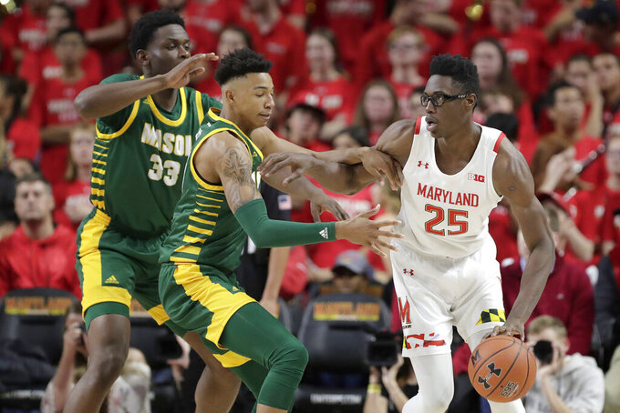 Maryland forward Jalen Smith (25) is defended by George Mason forward Greg Calixte (33) and guard Jordan Miller during the first half of an NCAA college basketball game Friday, Nov. 22, 2019, in College Park, Md. Maryland won 86-63. (AP Photo/Julio Cortez)