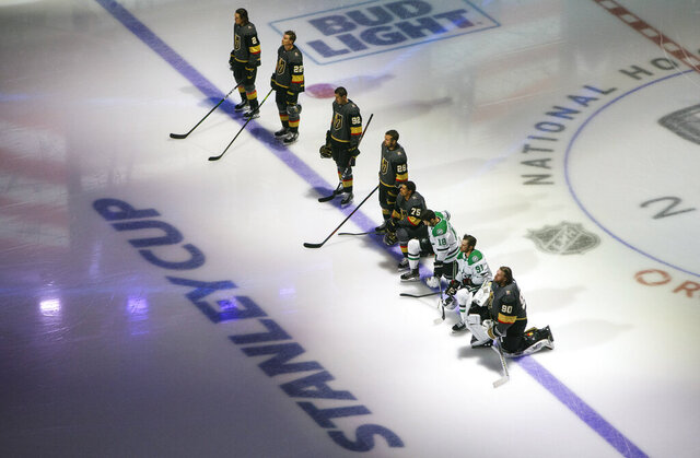 Dallas Stars' Jason Dickinson (18), Tyler Seguin (91) and Vegas Golden Knights' Ryan Reaves (75) and goalie Robin Lehner (90) take a knee for Black Lives Matter prior to an NHL hockey playoff game Monday, Aug. 3, 2020 in Edmonton, Alberta. (Jason Franson/The Canadian Press via AP)