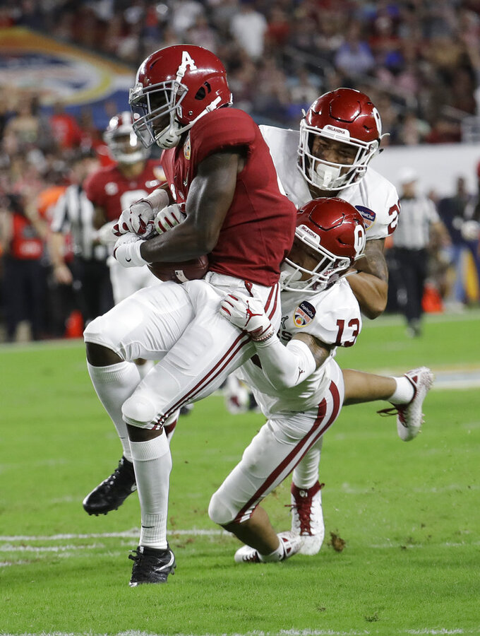 Oklahoma safety Robert Barnes (20) and cornerback Tre Norwood (13) tackle Alabama wide receiver Jerry Jeudy (4), during the first half of the Orange Bowl NCAA college football game, Saturday, Dec. 29, 2018, in Miami Gardens, Fla. (AP Photo/Lynne Sladky)
