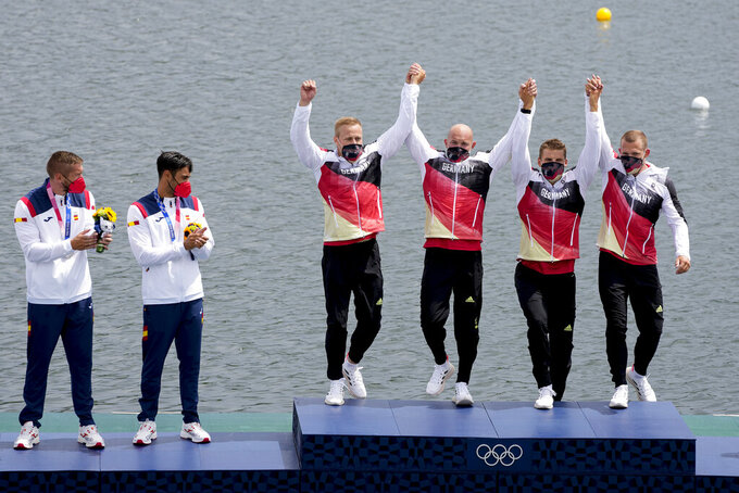 Max Rendschmidt, Ronald Rauhe, Tom Liebscher and Max Lemke of Germany step onto the podium for the medal ceremony after their gold medal finish in the men's kayak four 500m final at the 2020 Summer Olympics, Saturday, Aug. 7, 2021, in Tokyo, Japan. (AP Photo/Lee Jin-man)