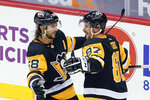 FILE - In this March 15, 2021, file photo, Pittsburgh Penguins' Sidney Crosby (87) celebrates with Kris Letang (58) after scoring against the Boston Bruins during the first period of an NHL hockey game in Pittsburgh. The Penguins and Islanders meet in Game 1 of their opening-round series on Sunday. The Islanders swept Pittsburgh in the first round of the playoffs in 2019. (AP Photo/Keith Srakocic)