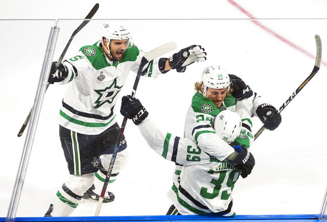 Dallas Stars defenseman Joel Hanley (39) celebrates his goal against the Tampa Bay Lightning with teammates Andrej Sekera (5) and Roope Hintz (24) during first-period NHL Stanley Cup finals hockey action in Edmonton, Alberta, Saturday, Sept. 19, 2020. (Jason Franson/The Canadian Press via AP)