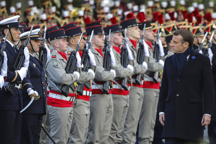 French President Emmanuel Macron reviews the troops as he inaugurates a memorial for soldiers fallen in foreign conflicts, Monday Nov. 11, 2019 in Paris. As part of commemorations marking 101 years since World War I's Armistice, French President Emmanuel Macron led a ceremony for the 549 French soldiers who died in 17 theaters of conflict since the 60s. (Ludovic Marin/Pool via AP)