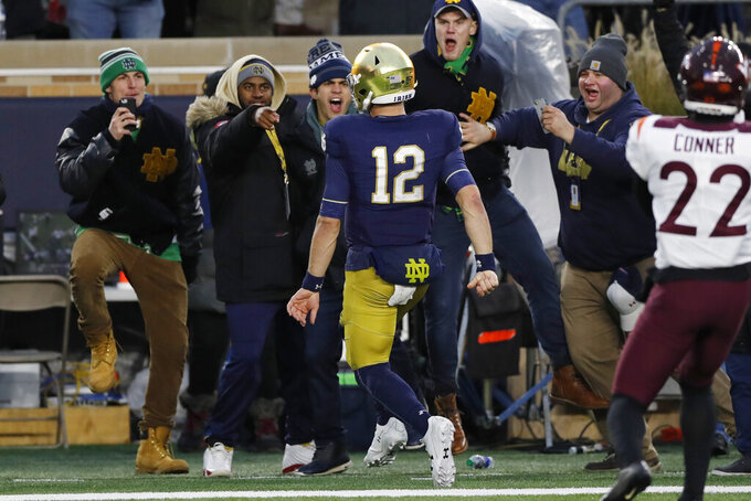 Notre Dame quarterback Ian Book (12) runs into the endzone for a 7-yard touchdown run during the second half of an NCAA college football game against Virginia Tech, Saturday, Nov. 2, 2019, in South Bend, Ind. (AP Photo/Carlos Osorio)