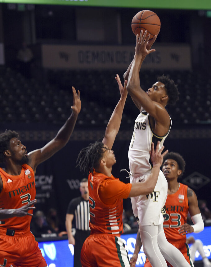 CORRECTS ID TO MIAMI'S ISAIAH WONG, NOT MIAMI'S DONALD CHANEY JR. - Wake Forest's Isaiah Mucius sinks a basket under pressure from Miami's Isaiah Wong during an NCAA college basketball game, Saturday, Jan. 30, 2021, at Joel Coliseum in Winston-Salem, N.C. (Walt Unks/The Winston-Salem Journal via AP)