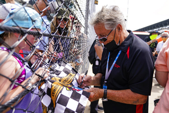 1969 Indianapolis 500 champion Mario Andretti signs autographs for fans during practice for the Indianapolis 500 auto race at Indianapolis Motor Speedway in Indianapolis, Friday, May 21, 2021. (AP Photo/Michael Conroy)