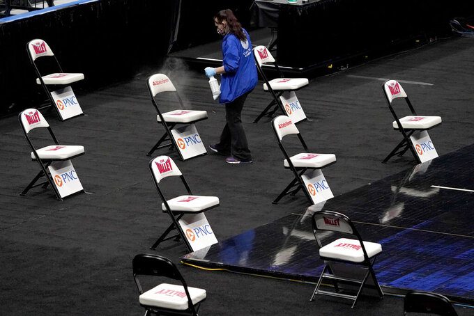 A worker cleans chairs serving as a socially distanced bench for teams after it was announced that an NCAA college basketball game in the quarterfinal round of the Missouri Valley Conference men's tournament between Northern Iowa and Drake has been cancelled Friday, March 5, 2021, in St. Louis. (AP Photo/Jeff Roberson)