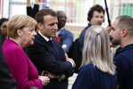 French President Emmanuel Macron, second left, and German Chancellor Angela Merkel talk to Airbus French and German employees after visiting the assembly line of the Airbus A350 in Toulouse, southwestern France, Wednesday, Oct.16, 2019. French President Emmanuel Macron and German Chancellor Angela Merkel are meeting in southern France, one day before a key EU summit that may approve a divorce deal with Britain. (AP Photo/Frederic Scheiber, Pool)