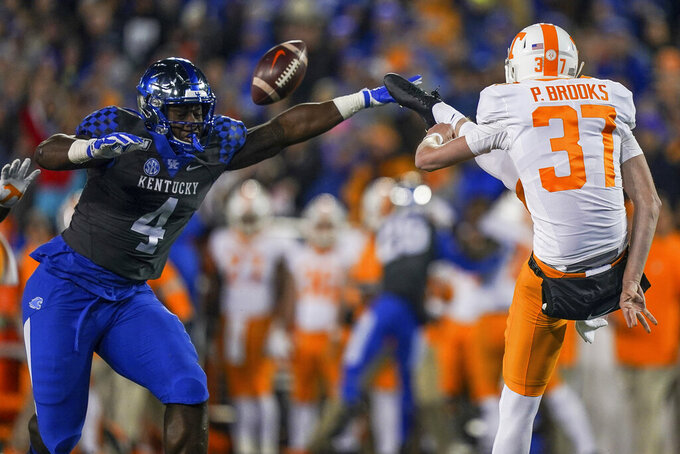 Kentucky defensive lineman Joshua Paschal (4) blocks the kick of Tennessee punter Paxton Brooks (37) during the first half of an NCAA college football game, Saturday, Nov. 9, 2019, in Lexington, Ky. (AP Photo/Bryan Woolston)