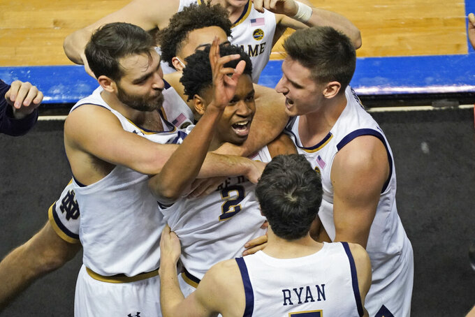Notre Dame guard Trey Wertz (2) who sank the game winning shot is swarmed by teammates after their 80-77 win over Wake Forest in the first round of the Atlantic Coast Conference tournament in Greensboro, N.C., Tuesday, March 9, 2021. (AP Photo/Gerry Broome)