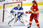St. Louis Blues goalie Jordan Binnington, left, looks on as Calgary Flames' Sean Monahan tries to tip the puck into the net during the third period of an NHL hockey game in Calgary, Saturday, Nov. 9, 2019. (Jeff McIntosh/The Canadian Press via AP)