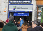 People queue to buy Christmas lottery tickets in Madrid, Spain, Saturday, Dec. 21, 2019. Spain's bumper Christmas lottery draw known as El Gordo, or The Fat One will be held on Dec. 22. (AP Photo/Paul White)
