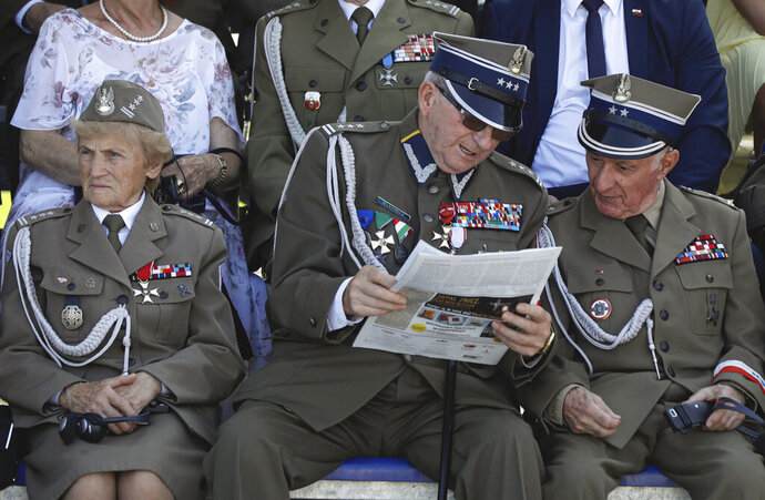 Polish war veterans look at a paper before a memorial ceremony marking the 80th anniversary of the start of World War II in Warsaw, Poland, Sunday, Sept. 1, 2019. (AP Photo/Petr David Josek)