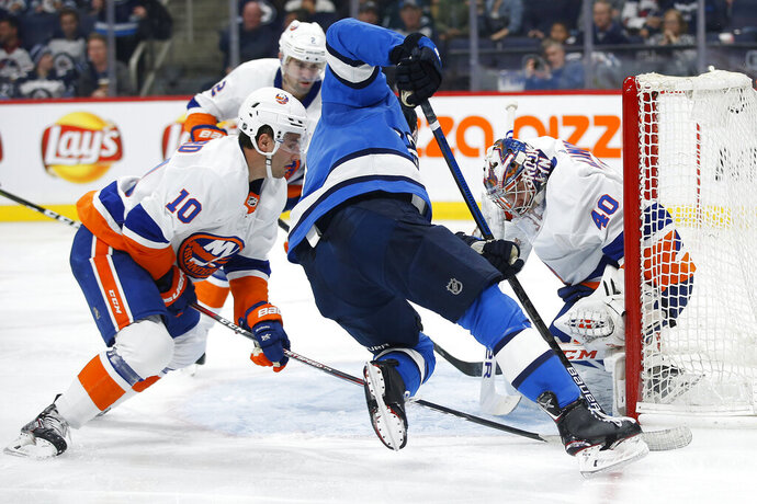 New York Islanders goaltender Semyon Varlamov (40) saves a shot from Winnipeg Jets' Andrew Copp (9) as he attempts to jam the puck in as Islanders' Derick Brassard (10) defends during the second period of an NHL hockey game Thursday, Oct. 17, 2019, in Winnipeg, Manitoba. (John Woods/The Canadian Press via AP)