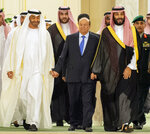 In this photo released by the Saudi Royal Palace, Yemen's president, Abed Rabbo Mansour Hadi, center, is accompanied by Saudi Arabia's Crown Prince Mohammed bin Salman, right, and Dhabi's crown prince, Mohammed bin Zayed Al Nahyan before signing a power-sharing deal in Riyadh, Saudi Arabia, Tuesday, Nov. 5, 2019. Yemen's internationally recognized government has signed a power-sharing deal with Yemeni separatists that are backed by the United Arab Emirates. The deal aims to halt months of infighting between the two groups. (Bandar Aljaloud/Saudi Royal Palace via AP)