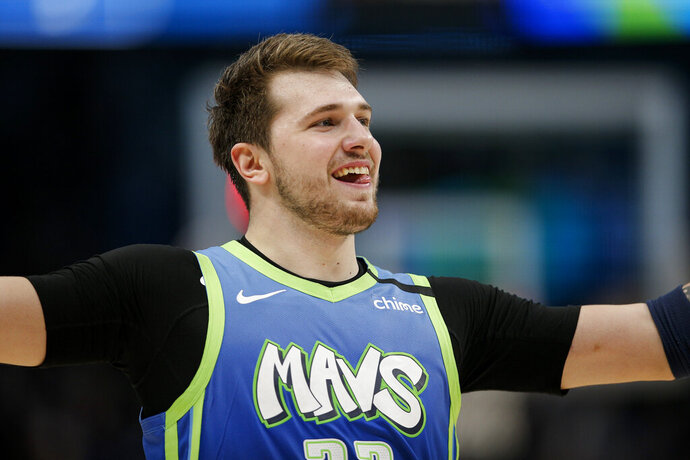 Dallas Mavericks forward Luka Doncic celebrates during a timeout in the second half of the team's NBA basketball game against the Portland Trail Blazers, Friday, Jan. 17, 2020, in Dallas. The Mavericks won 120-112. (AP Photo/Brandon Wade)