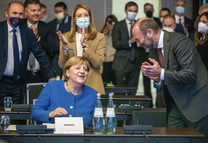 German Chancellor Angela Merkel, front left, accepts the applause next to Manfred Weber, front right, Chairman of the EPP Group, at the beginning of the closed session of the EPP Group Bureau of the European Parliament in Berlin, Germany, Thursday, Sept. 9, 2021. (Michael Kappeler/dpa via AP)