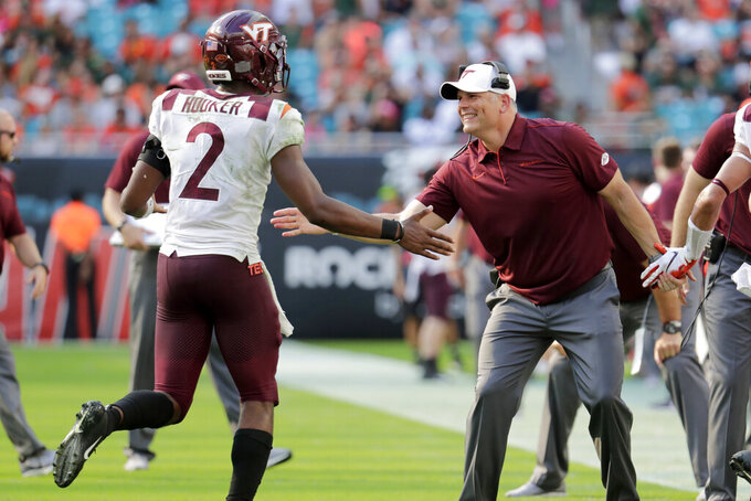 Virginia head coach Justin Fuente, right, greets quarterback Hendon Hooker (2) after a touchdown during the first half of an NCAA college football game against Miami, Saturday, Oct. 5, 2019, in Miami Gardens, Fla. (AP Photo/Lynne Sladky)