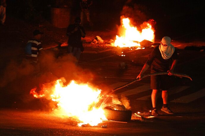 Demonstrators set up burning barricades to block a street during a protest demanding the resignation of President Juan Orlando Hernandez, in Tegucigalpa, Honduras, late Friday, Oct. 18, 2019. The protests come after Tony Hernandez, the brother of President Juan Orlando Hernandez, was convicted in a massive drug conspiracy, that prosecutors of the New York federal court say was protected by the Central American country's government. (AP Photo/Elmer Martinez)