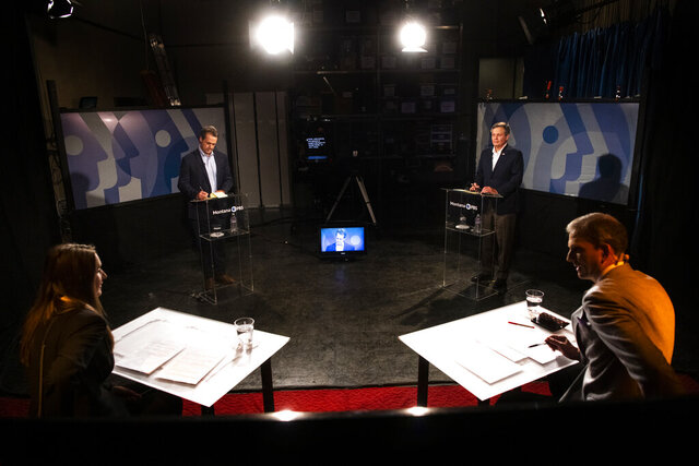 Gov. Steve Bullock, back left, and U.S. Sen. Steve Daines, R-Mont., back right, prepare for their televised debate on Montana PBS at the KUFM-TV studio at the University of Montana on Monday, Sept. 28, 2020, in Missoula, Mont. (Ben Allan Smith/The Missoulian via AP)