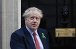Britain's Prime Minister Boris Johnson looks up from the doorstep of 10 Downing Street in London, Thursday, Oct. 10, 2019. Johnson was meeting mental health campaigners, whose badge he wears and later Thursday he is scheduled to meet with Irish Prime Minister Leo Varadkar for talks on Brexit. (AP Photo/Alastair Grant)